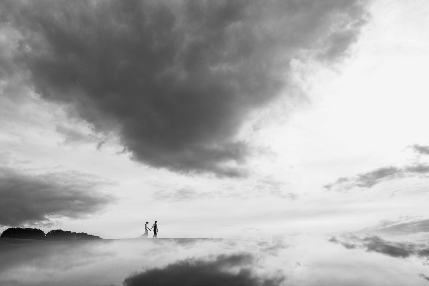 THe bride and groom walking in the clouds