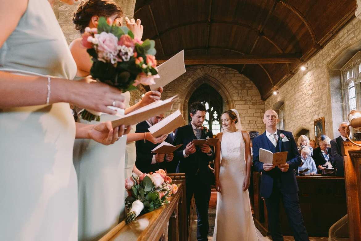 The bride and groom in the church sing a hymn