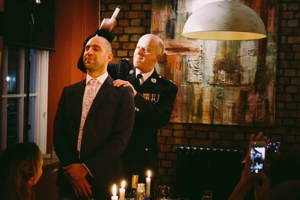 A wedding guests demonstrates a story about a sink plunger on the stag do