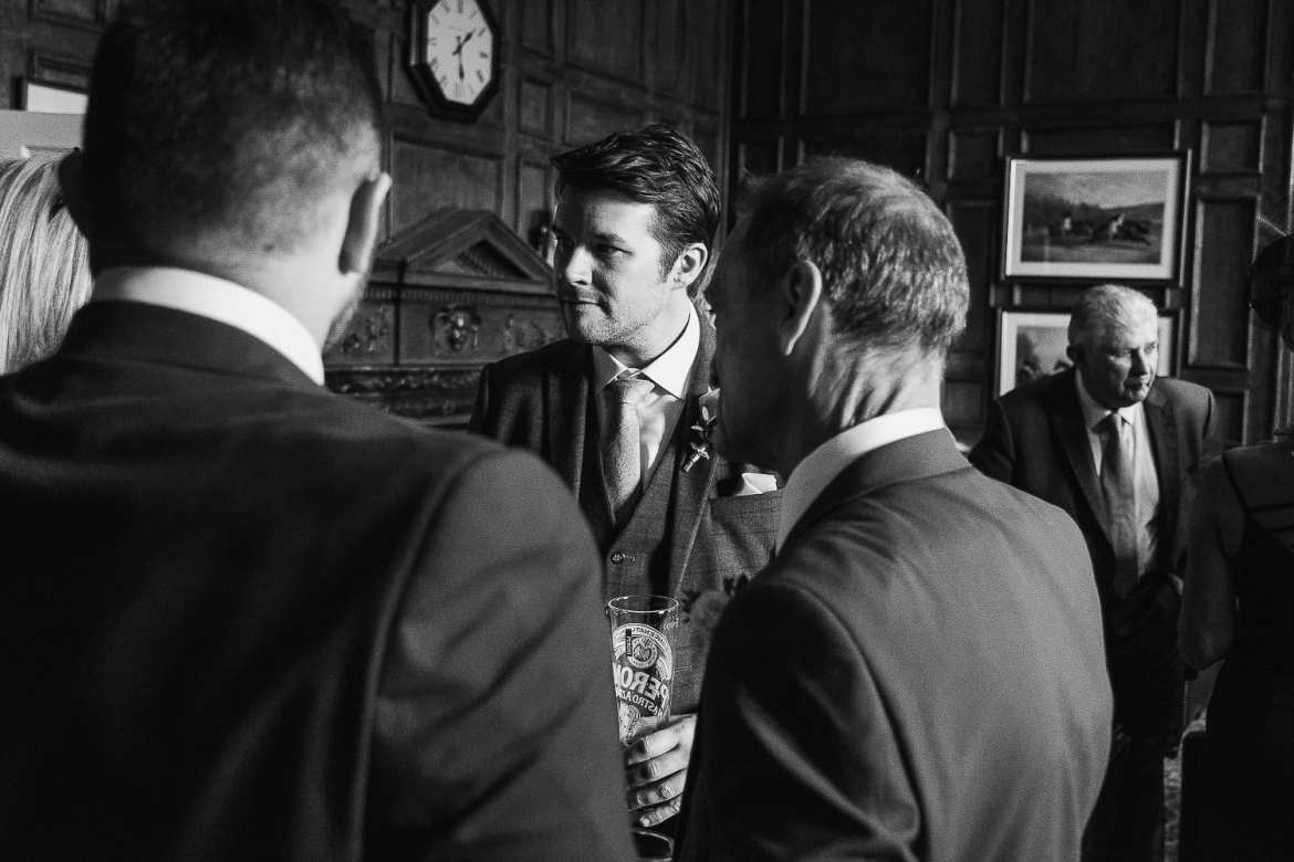 The groom chats to some of the wedding guests in the bar