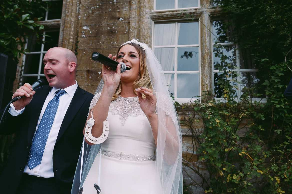 The bride and one of the guests singing during the drinks reception on the terrace