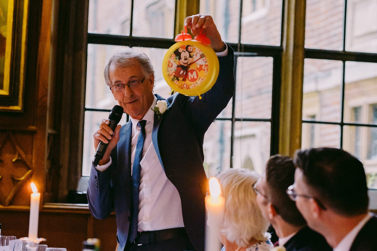 The father of the groom holds up a clock