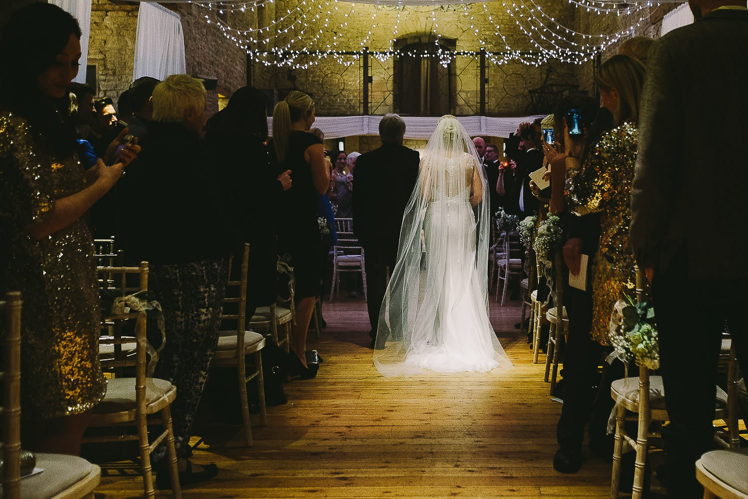 The bride and her father walk down the aisle at The Great Tythe Barn