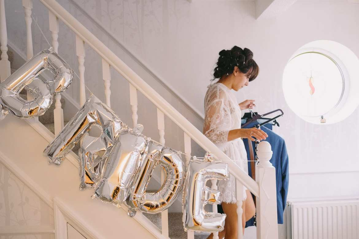 the bride comes down the stairs which are decorated with balloons spelling out the word bride