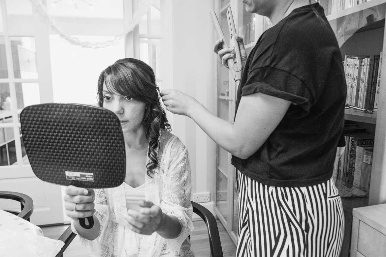 the bride checks her hair in a mirror