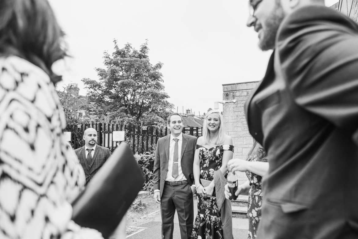 wedding guests laughing outside the church