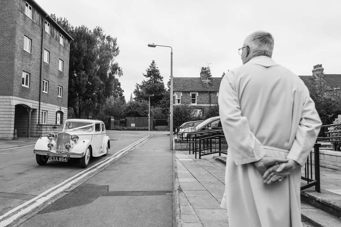 The wedding car arrives at the church as the vicar looks on