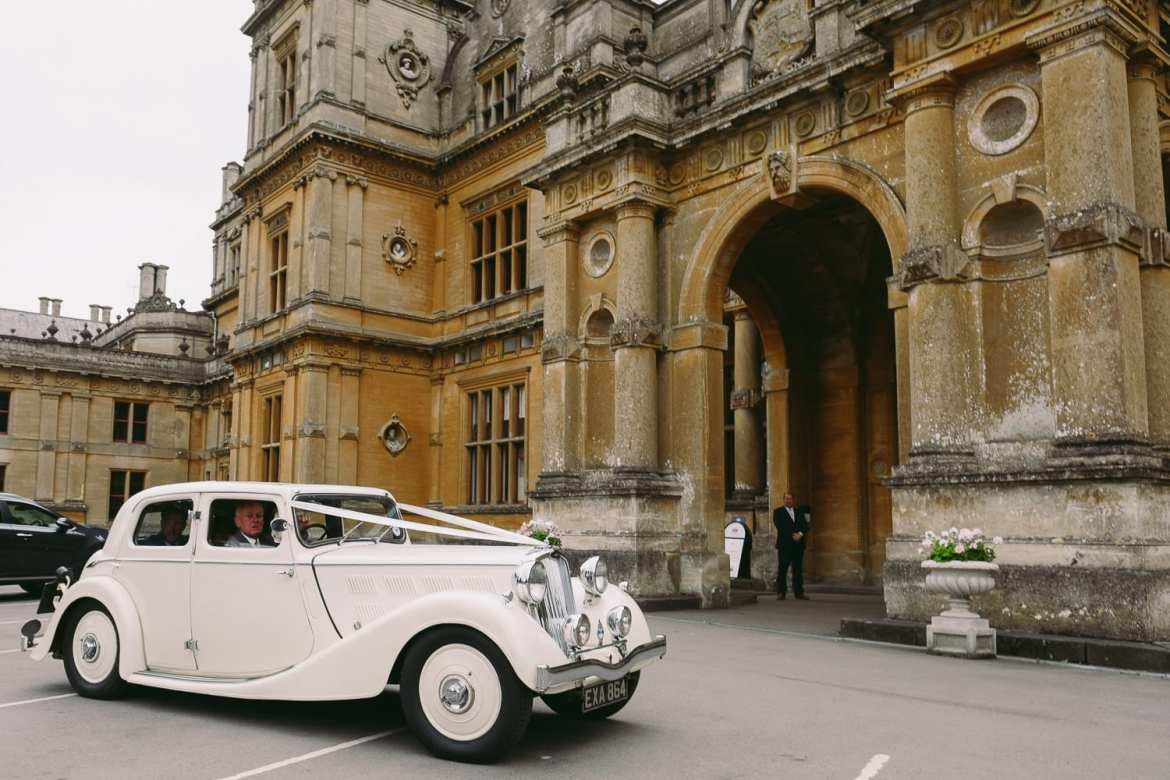 The bride and groom in the wedding car arrive at Westonbirt House