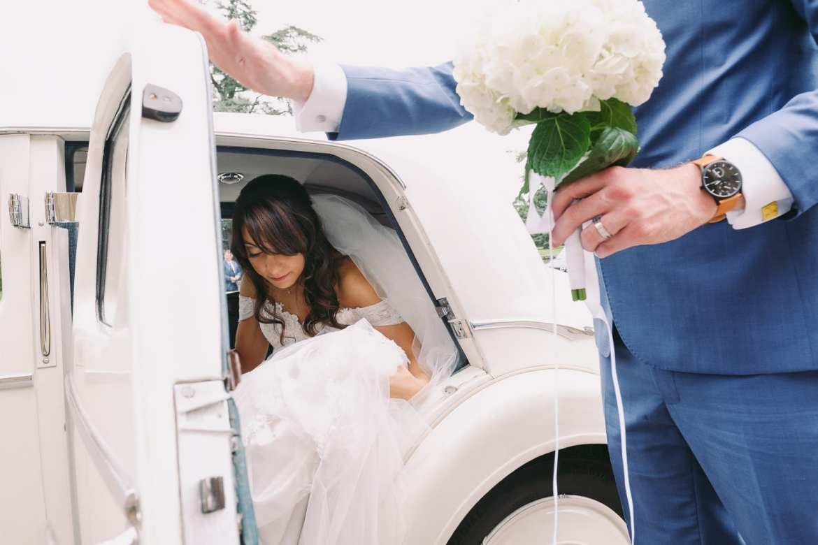 the groom holds the door as the bride gets out of the wedding car