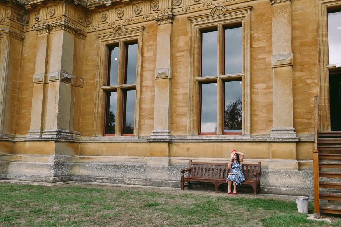 a pregnant wedding guest sat on a bench outside westonbirt school takes a selfie