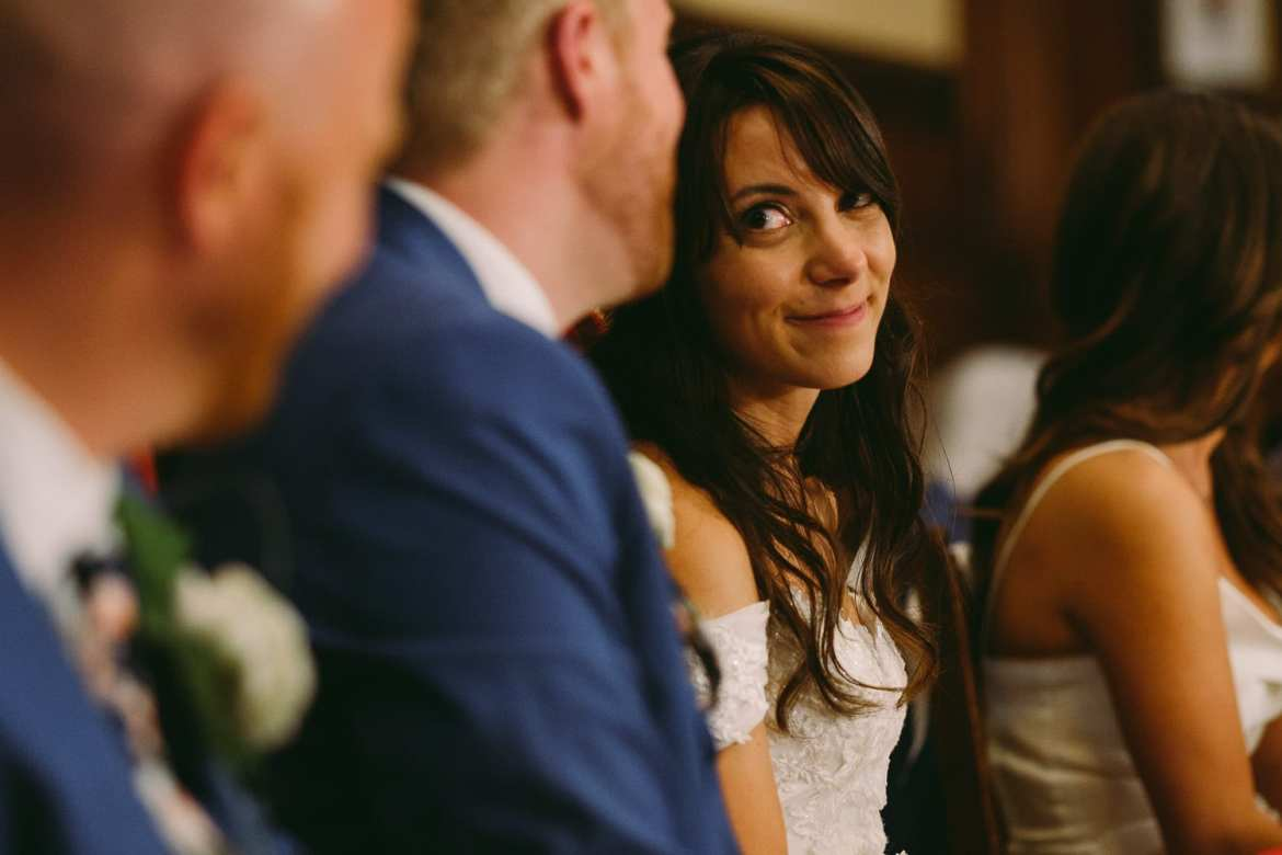 the bride smiles at the groom during the speeches