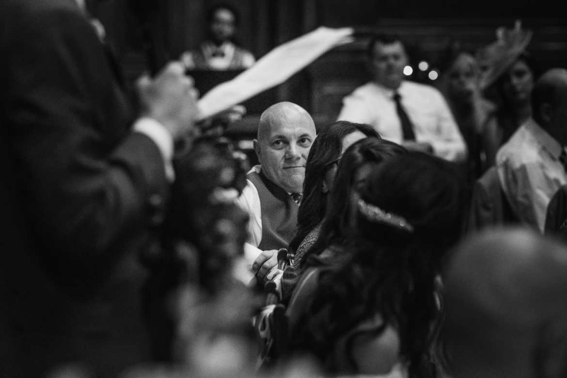 the father of the bride watches the groom