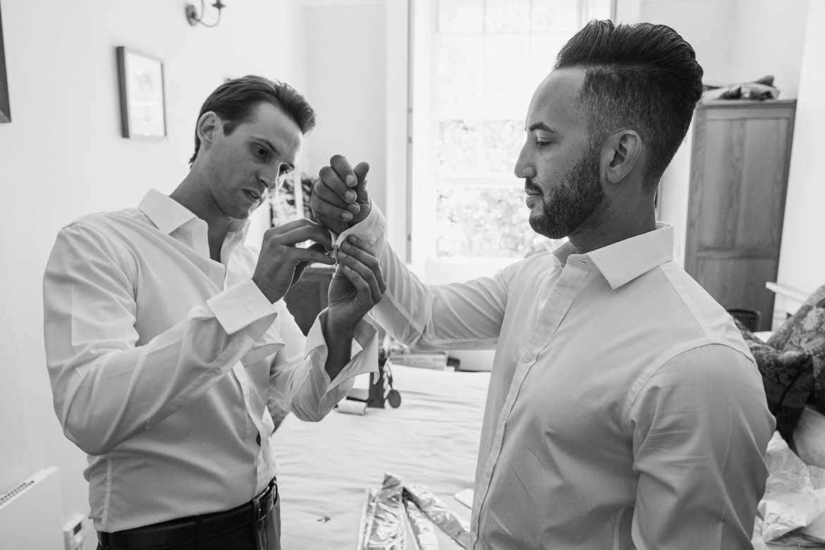 Two grooms getting dressed