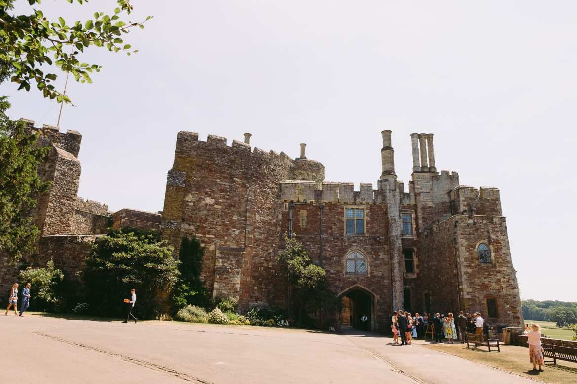 Wedding guests gather in the sunshine outside Berkeley Castle