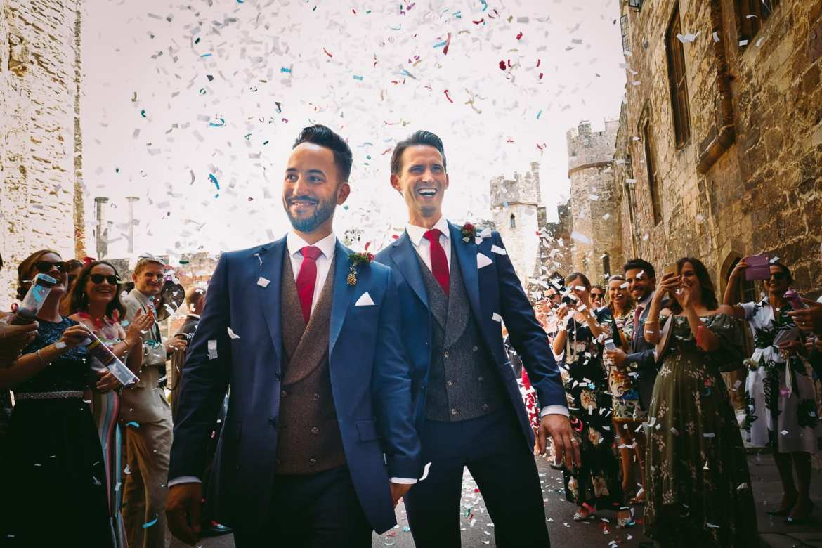 Confetti cannons are fired as the grooms walk out on to the gun terrace