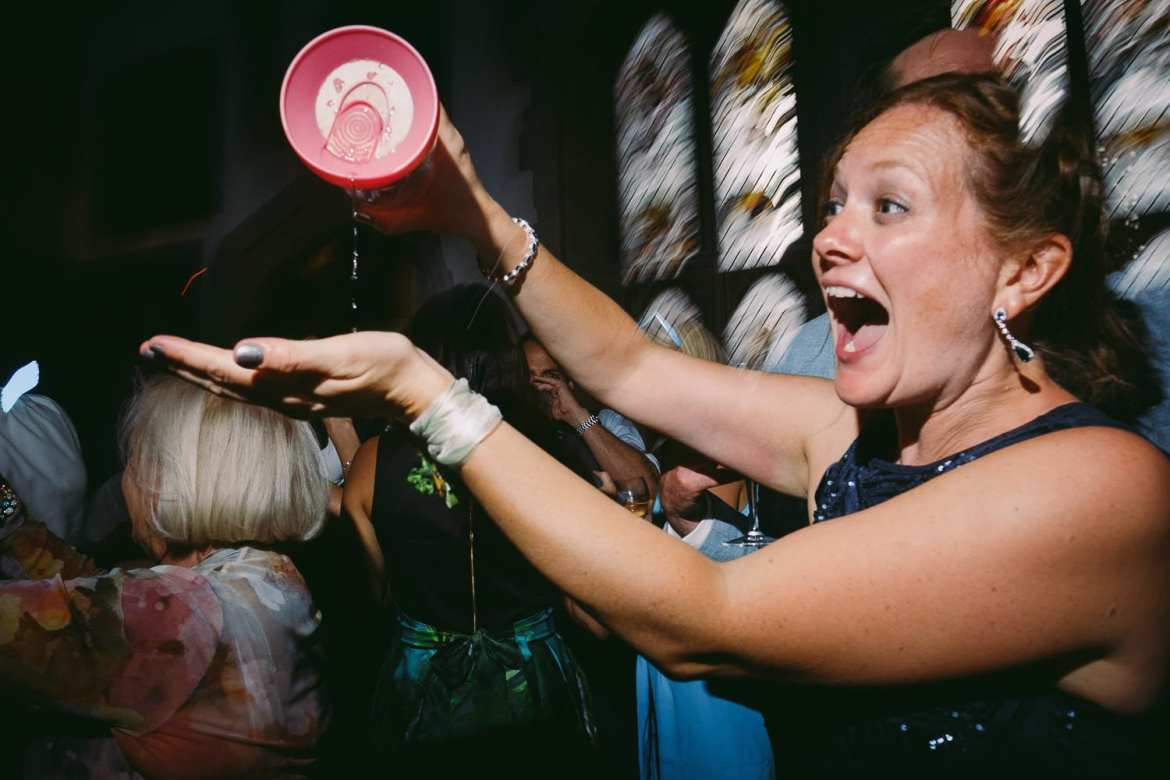 A bridesmaid pours wine from her safety cup
