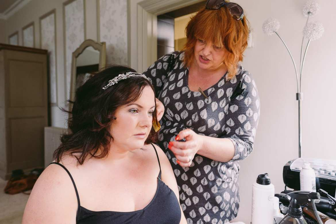Bride having her hair done in the morning