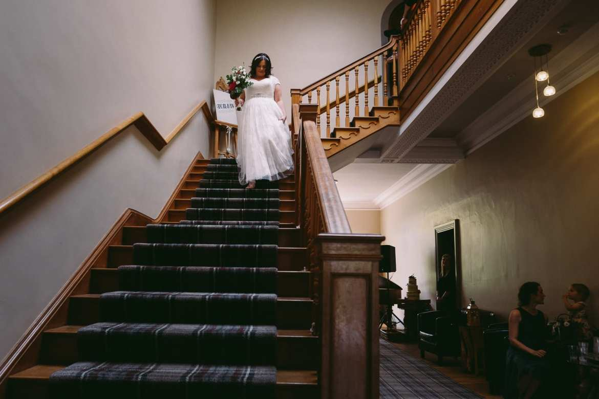 Bride coming down the stairs before the ceremony