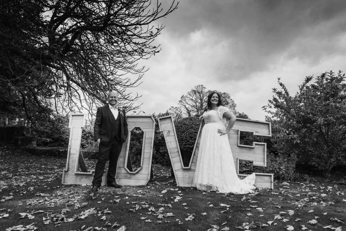 Bride and groom next to the love sign on the lawn