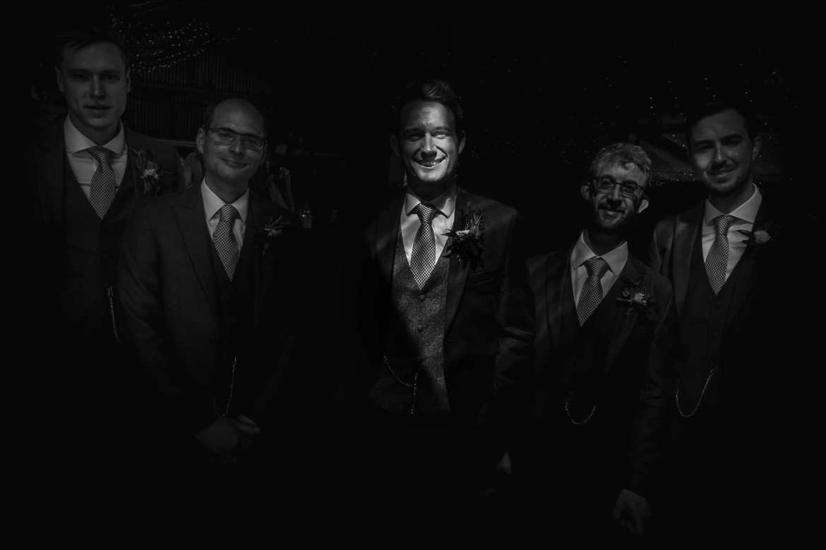 The groom and groomsmen in a shaft of like