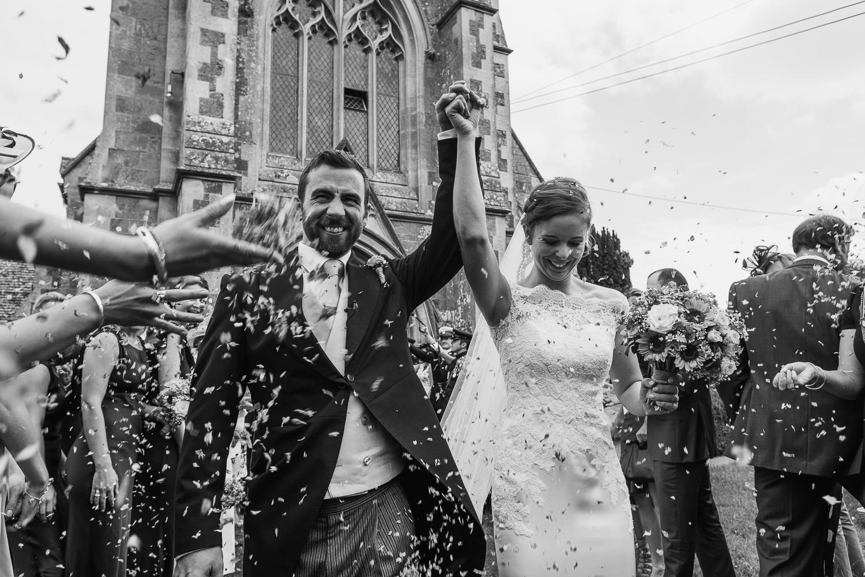Newlyweds confetti walk from the church