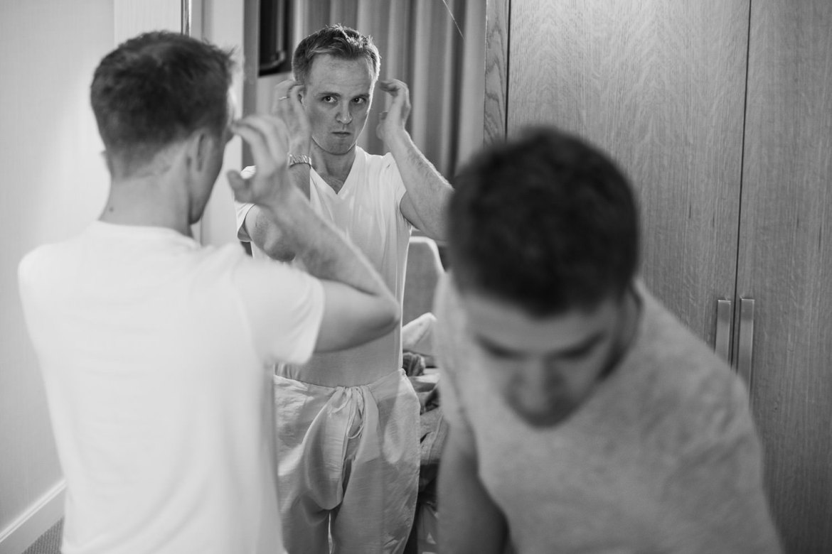 Groom checking his hair in the mirror during the morning preparations