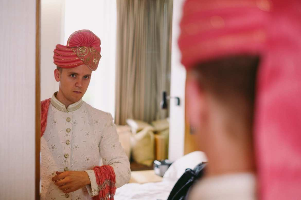 Groom putting on his traditional Indian hat for the ceremony