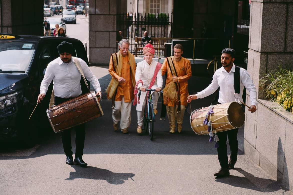 The groom arrives on his bike accompanied by Dhol drummers