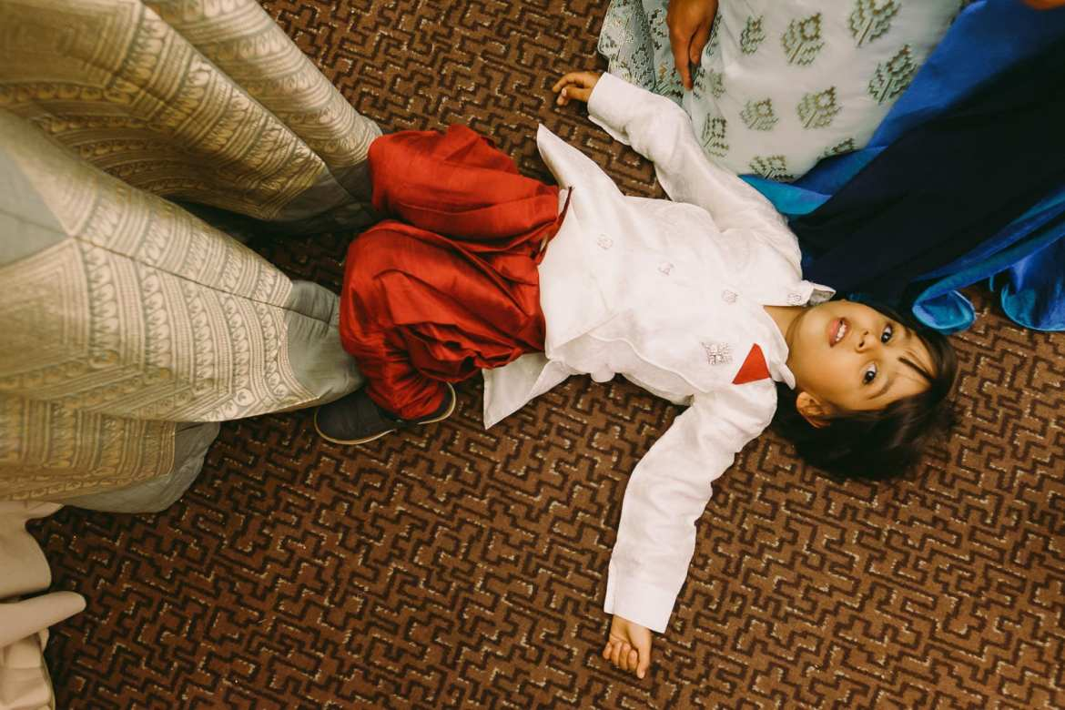 Child in Indian robes lying on the floor