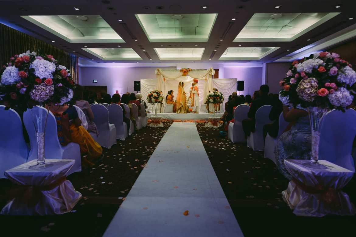 The bride and groom and their families in the Indian mandap
