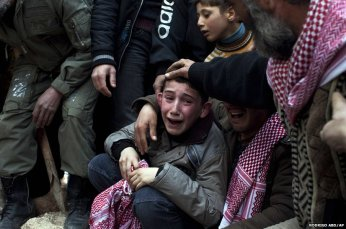A Syrian boy, Ahmed, mourns his father, Abdulaziz Abu Ahmed Khrer, who was killed by a Syrian Army sniper. (Photo by Rodrigo Abd).