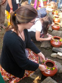 Affixing a string of flowers around the clay pot.