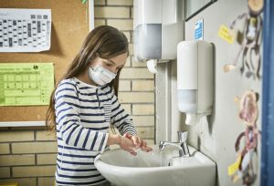 girl with face mask washing hands