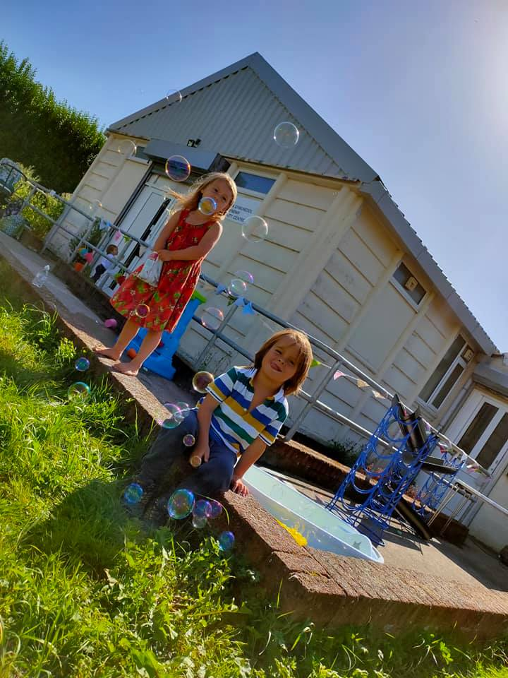 Two young children play with bubbles in the sunshine