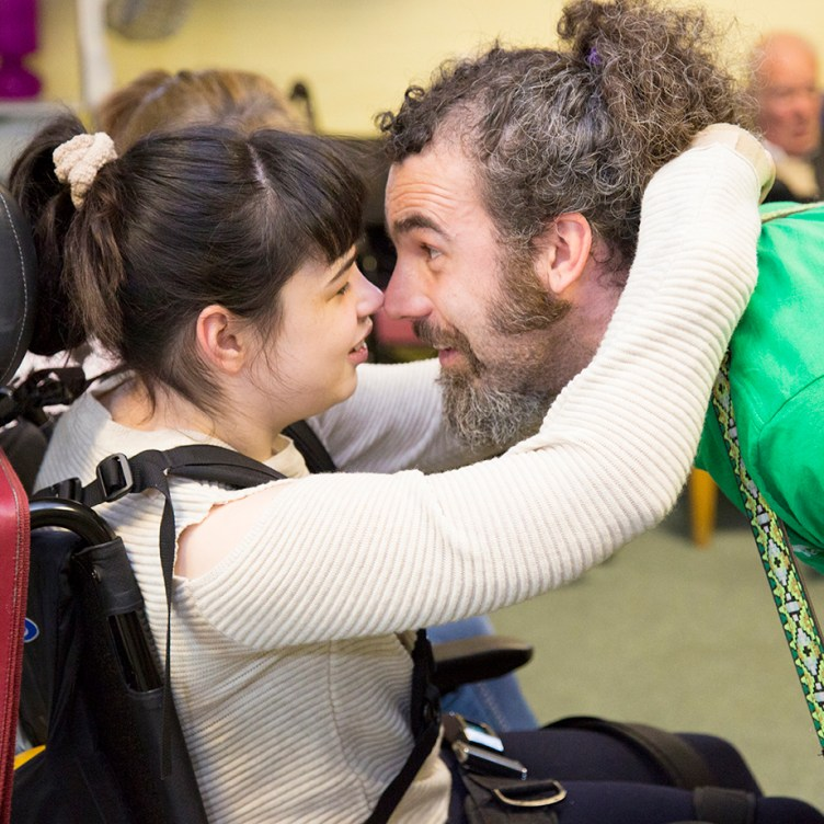 A smiling young girl in a wheelchair rubs noses and hugs KeyCreate's Dave