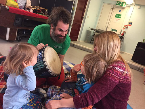 A family sit around a djembe drum encouraging a young boy to play it as he smiles