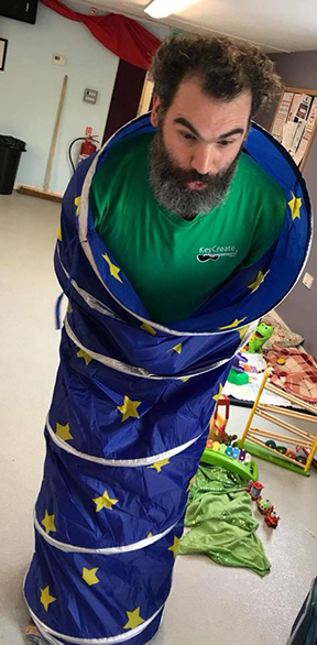 a bearded man, dave of keycreate, stands inside a play tunnel and makes a comical expression