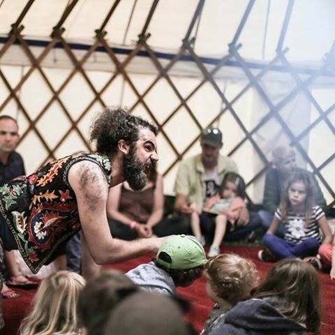 A group of adults and children watch KeyCreate perform a story and Dave makes a monster face while crawling on all fours in a yurt at Blue Lagoon Festival