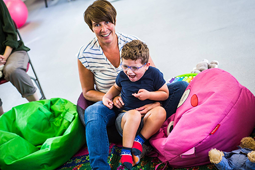 A young boy with additional needs sits on the lap of his support worker. Both are smiling while participating in playgroup.