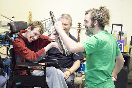 Keycreate's Dave supports a man in a wheelchair to enjoy making sounds with chimes.