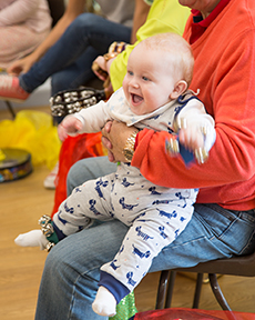 a young infant in a baby grow smiles as he sits on the lap of someone holding him