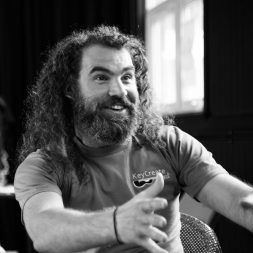 Dave of Keycreate with arms outstretched and sporting a full beard, curly hair and a joyful expression.