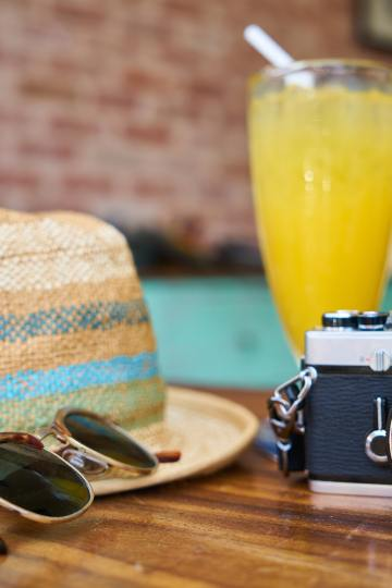 hat sunglasses camera and drink on a table