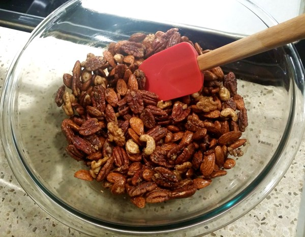 Pecans and nuts in a bowl getting coated to bake