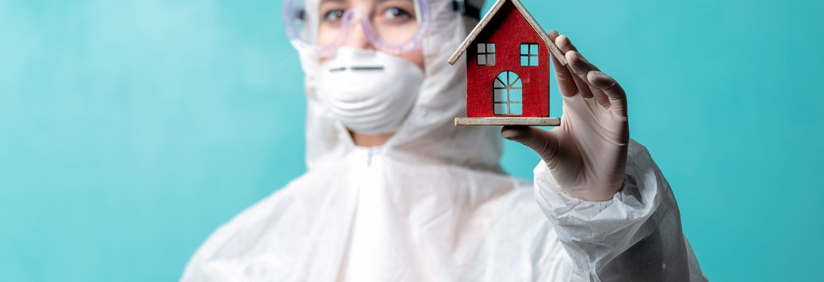 A medical professional wearing protective gear holding a small model of a house