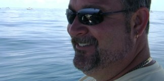 A man sitting on a boat looking at the camera - Sunglasses