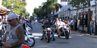 A group of people riding a motorcycle on a city street - Motorcycle