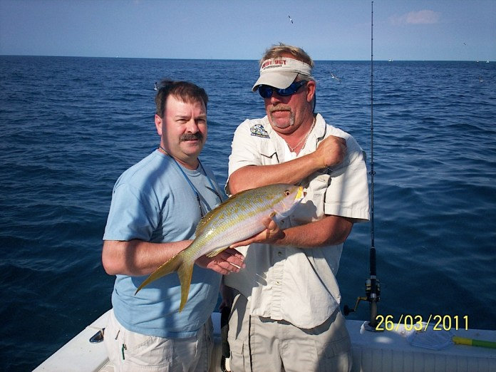 A man holding a fish on a boat in a body of water - Big-game fishing