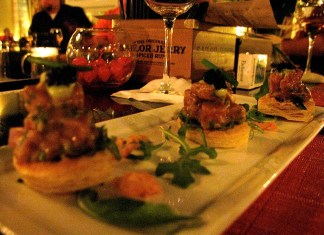 A plate of food and glasses of wine on a table - Pincho