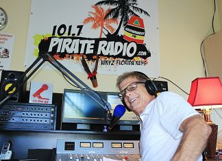 A man standing in front of a television playing a video game - Pirate Radio Key West